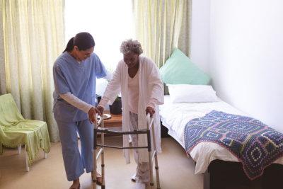nursing assistant assisting senior woman on walker
