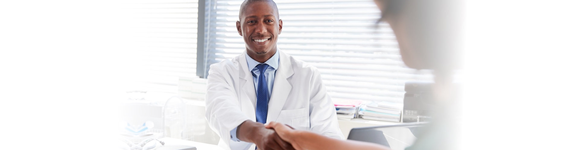 doctor shaking hans with a patient on his office